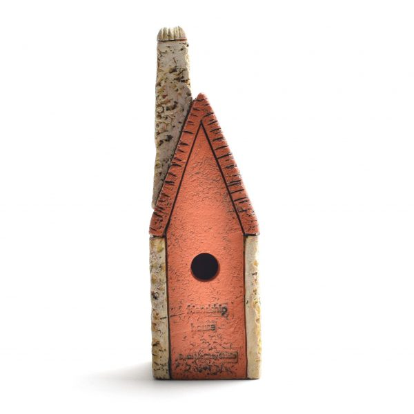view of back of clay house sculpture with hole for wall hanging,
