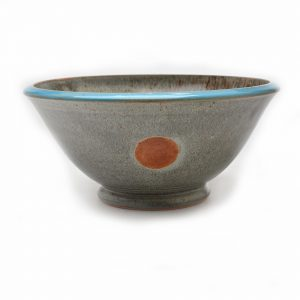 gray wheel thrown cereal bowl with a blue rim and red dot