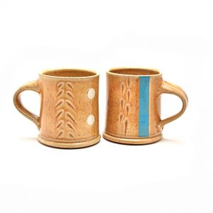 tan straight sided mugs with carvings and blue stripe