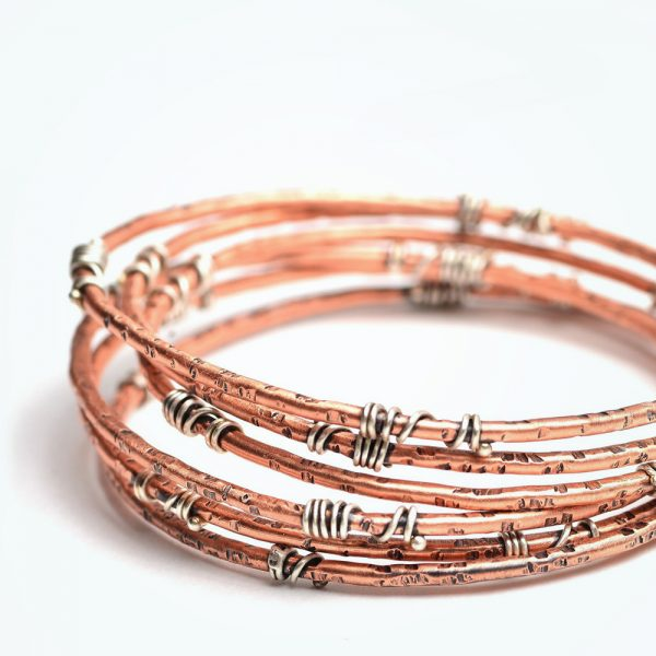 copper handmade bangle bracelet with silver wrapped around it