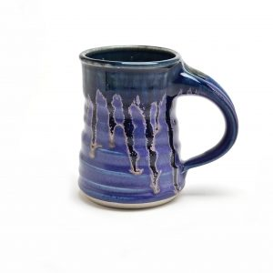 Cobalt blue wheel thrown ceramic pottery mug with darker blue drips around the edge