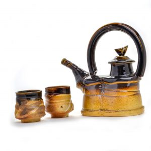 teapot set by sue grier, fired in a wood kiln, top is yellow and top is dark brown