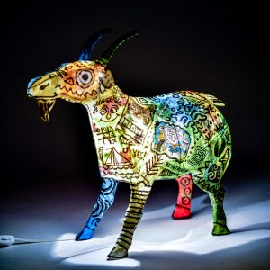 light up goat lamp with black writing, blue red green and yellow paper mache