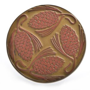 straight shot of round yellow ceramic pine cone tile trivet made with red clay