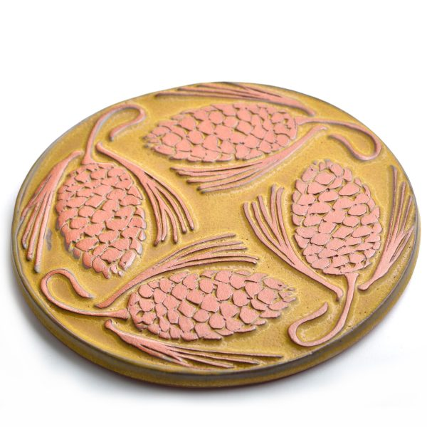 Yellow round pine cone trivet tile made of red clay handmade in asheville nc
