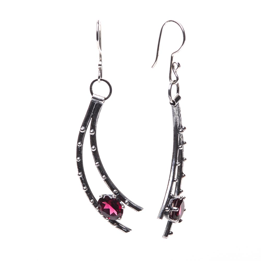 side view of garnet and silver earrings, curved silver earrings holding a faceted garnet at the bottom, handmade forged silver earrings with garnet, fancy jewelry, asheville jeweler