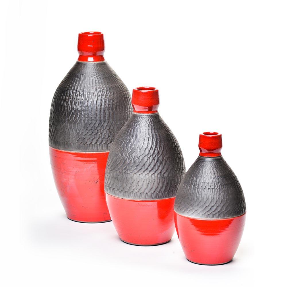 group of red and black raku bottles