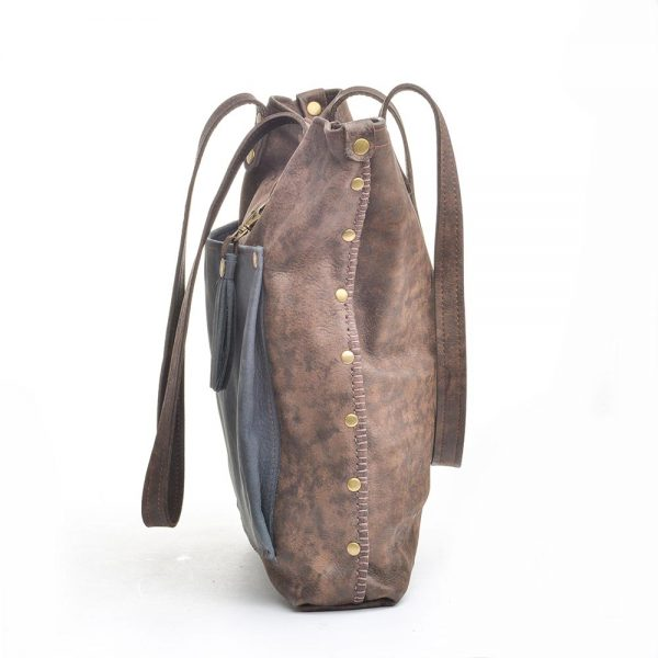 side view of brown leather bag with blue pocket, leather with rivets and hand stitching
