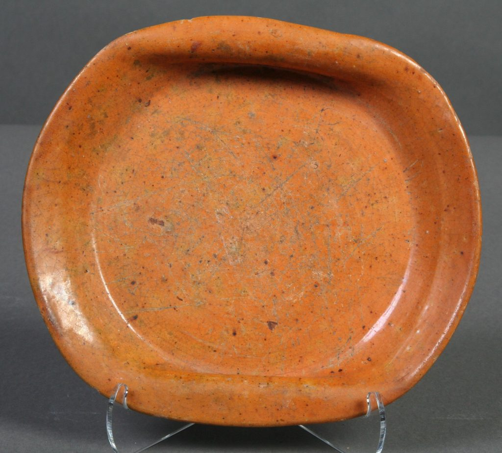 Plate, Jugtown Pottery, c. 1930, earthenware - shallow plate with two altered sides. Burnt orange glaze. Made in Seagrove, NC. Gift of Frances Goodrich.