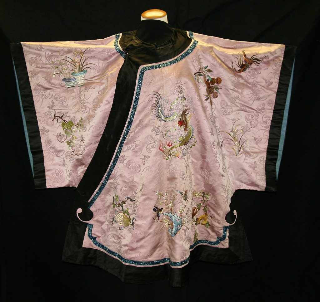 Robe, unknown artist, Chinese, c. 1890, silk - a women's robe handwoven with butterflies and narcissus flowers, with many symbolic embroidered elements stitched to the pink silk. These elements included dragon, gourds, citron, bats, narcissus flower, fruit, fish, birds, plum blossoms, figs, Buddha's hand and bamboo. Made for informal wear. There is a light blue lining to the robe and the hem and sleeves are trimmed in black silk. The robe wraps around the wearers body and is secured with black fabric knot and loop closures.