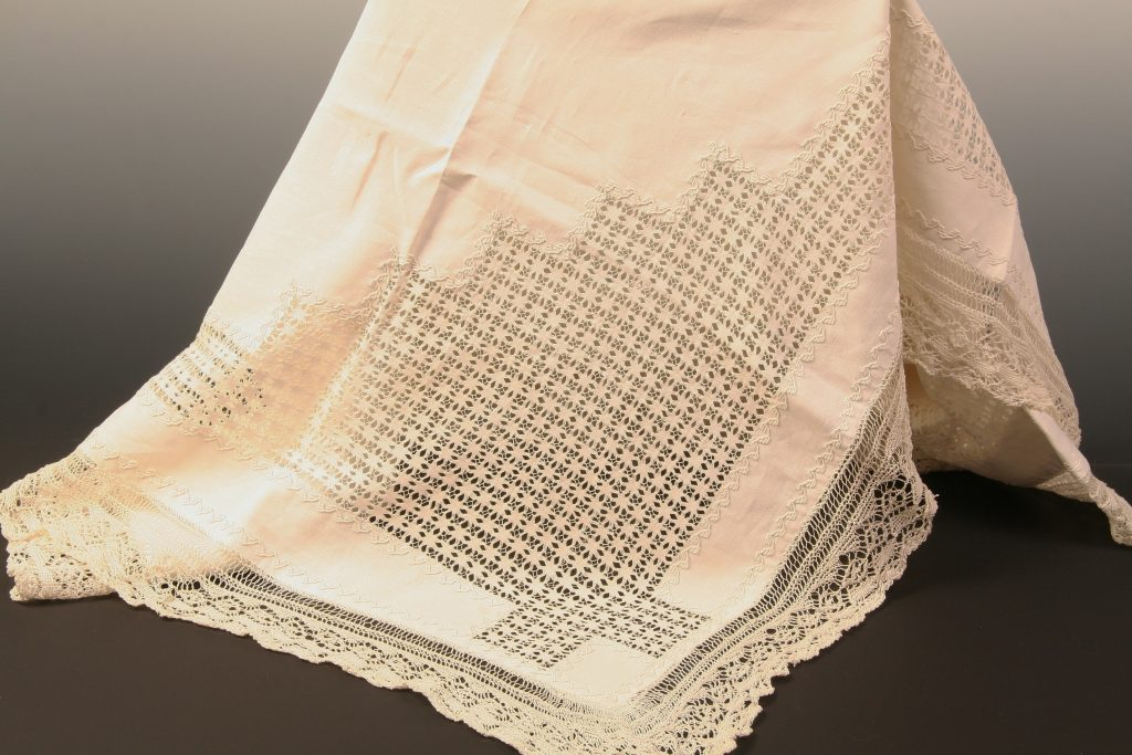 "Drawn Thread Linen Tea Cloth, Margaret Hodges, Scottish, c. 1880, A very fine handwoven, linen tea cloth. The decoration on the cloth proper is accomplished through the drawn thread technique. The ""fringe"" around the edge of the tea cloth is expertly knitted. The drawn thread pattern creates the corners and border of the cloth. In the center of the cloth a drawn thread cross with a square in each of the four quadrants is visible."