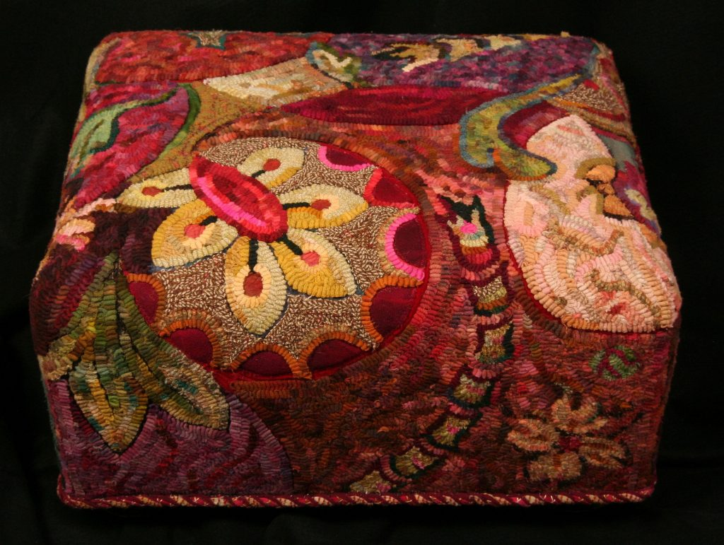 Contemporary Stool, Kim Nixon, 2002, hooked rug upholstered stool, floral and fauna patterned on top of shades of red and purple background. There is an intentional piece missing in the hooked pattern - it was a study by the artist of the positive and negative dimensions of wool applied to the surface and wool hooked to the backing. The edge is hand embroidered by the artist. Hand dyed wool by the artist.