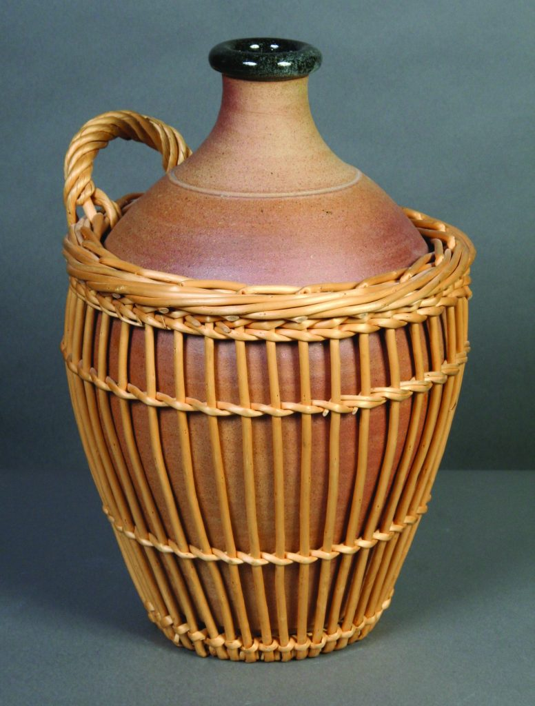 Jug in Basket, John Leach, 1987, stoneware - large woodfired jug, unglazed exterior, glazed interior, rim  in black color. Handwoven willow (fitching) around jug up to mid shoulder with one carrying handle.