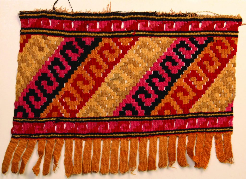 Chancay Tapestry, Peruvian, c. AD 1000-1450, textile - a hand woven, hand dyed, Peruvian tapestry weaving. The main section of the tapestry is a diagonal pattern created by the slit stitch technique from the Chancay culture from the central coast of Peru. This main section is separated by a horizontal border on the top and bottom. The weaving is made up of several colors - red, mauve, brown, light brown, and black. There is fringe on one side of the weaving. The opposite side is frayed. The weaving was a gift to SHCG Director Emertus Bob Gray and his wife Verdelle when they attended the Worlds Crafts Conference in Lima, Peru in the early 1980s.
