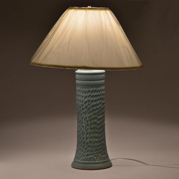 tall ceramic turquoise lamp with light on in the dark
