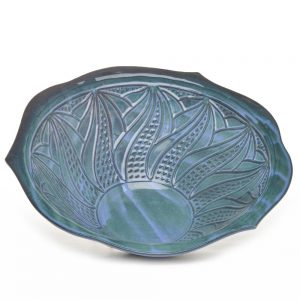inside carved lines in a large blue green ceramic cereal bowl