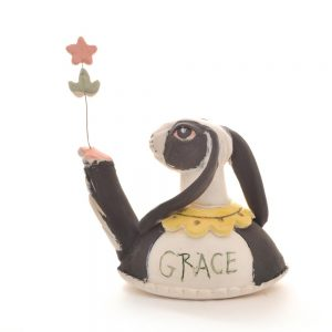 bunny sculpture holding a flower with grace drawn on the back
