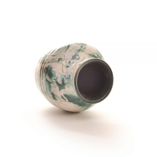 small blue green and white bud vase laying on its side