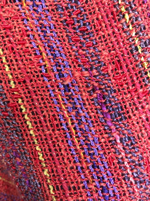 detail of orange sunset colored handwoven cotton swoop poncho
