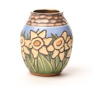 handmade and hand carved arts and crafts style ceramic vase with yellow daffodils and a blue sky