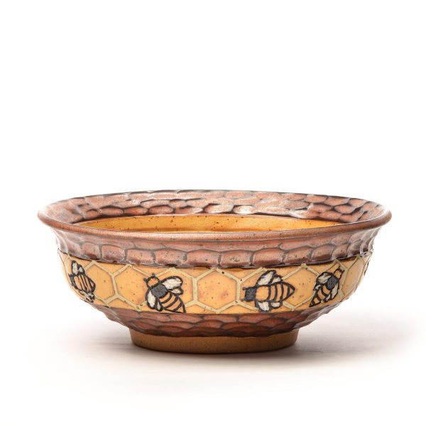 handmade ceramic bowl with carved bees and honey comb with bright yellow interior glaze