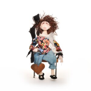 handmade cloth doll with handpainted face holding a rusty heart sitting on a bench