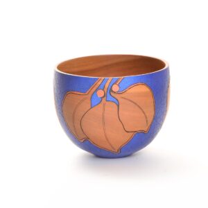bright blue painted wood bowl with cherry leaves and berries
