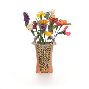 handmade corn shuck flowers in a carved soda fired joy tanner basket base
