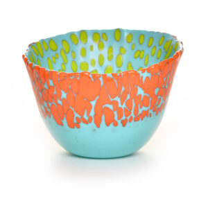 large slumped turquoise glass bowl with green and orange dots around the rim