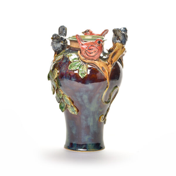 sculptural ceramic vase with vines leaves and birds perched on top