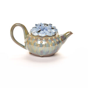 handmade green ceramic teapot with blue hydrangeas on the lid