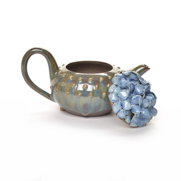 handmade green ceramic teapot with blue hydrangeas on the lid