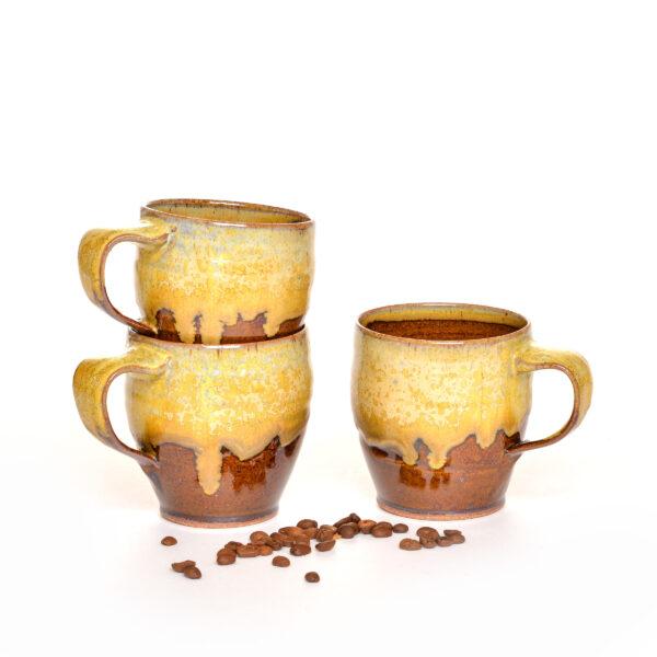 drippy brown glazed mugs with a tan drippy glaze around the rim