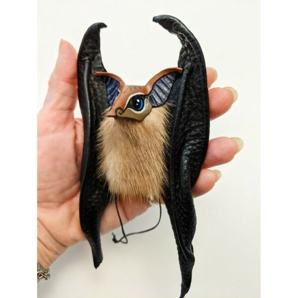 Leather bat ornament. Hand tooled and painted veg tanned leather head using Angelus leather paint. Cow hide sewn wings, repurposed mink fur body.