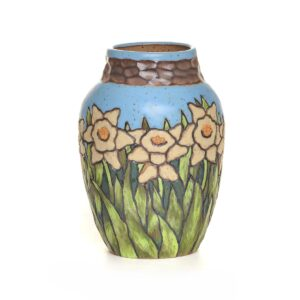 handmade ceramic vase with daffodils and blue sky surrounding the whole vase