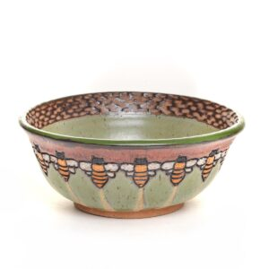 handmade ceramic bowl with bees around the outside and green glaze inside