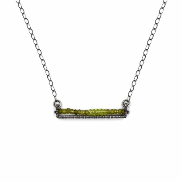 handmade oxidized silver necklace with a line of small peridot gemstones, asheville jeweler, august birthstone handmade necklace