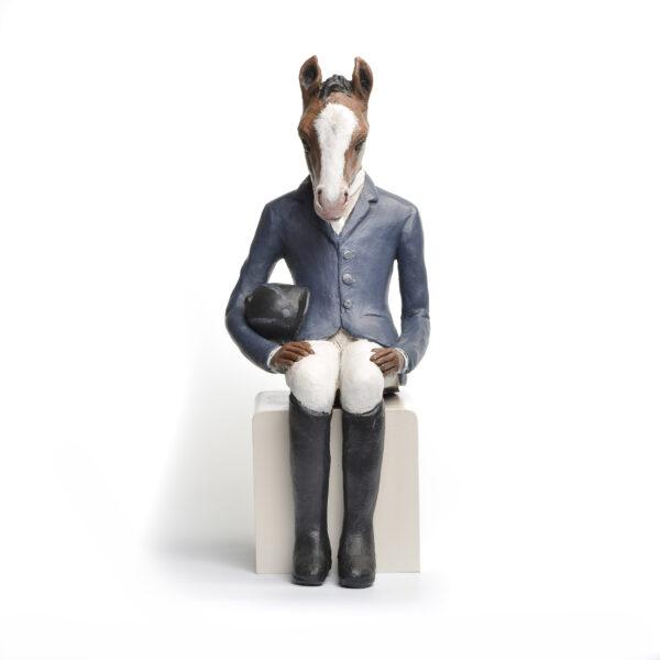 sitting horse sculpture wearing horse riding gear
