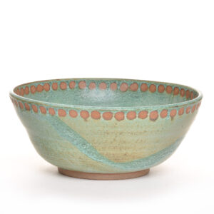 green handmade ceramic serving bowl with dots around the rim
