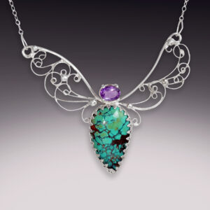 large silver filigree necklace with a large turquoise stone and amethyst